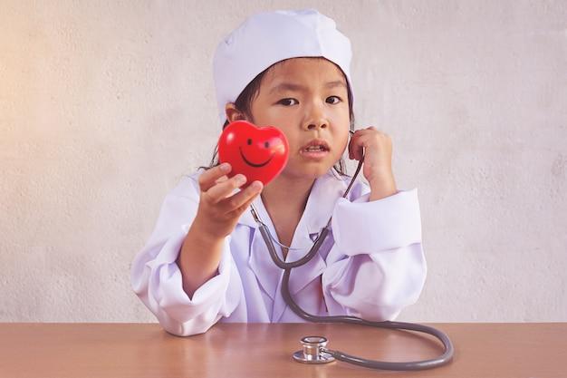 Asiatisches mädchen, das als gesundes herz der doktorpflege spielt Premium Fotos