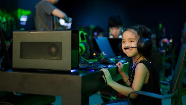 Asiatisches mädchen, das computerspiele im internet-café spielt Premium Fotos