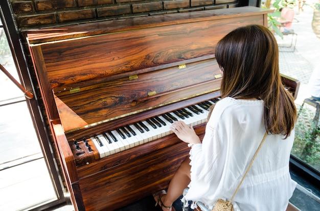 Asiatisches mädchen, das klavier spielt Premium Fotos