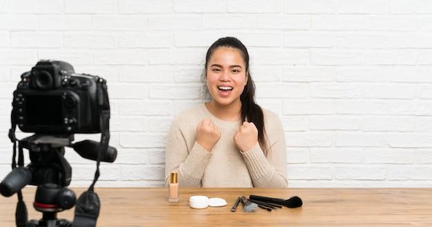 Asiatisches mädchen des jungen bloggers, das ein videotutorium feiert einen sieg notiert Premium Fotos