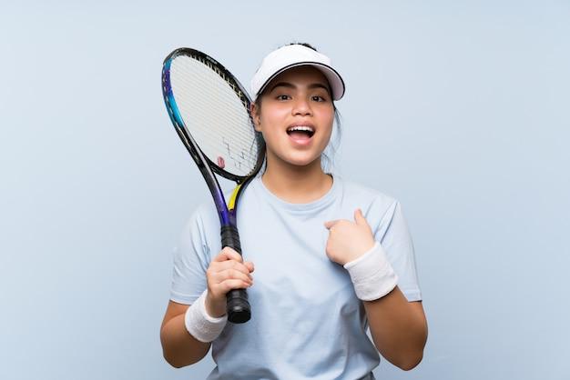 Asiatisches mädchen des jungen jugendlichen, das tennis mit überraschungsgesichtsausdruck spielt Premium Fotos