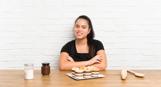 Asiatisches mädchen des jungen jugendlichen mit lots muffinkuchenlachen Premium Fotos