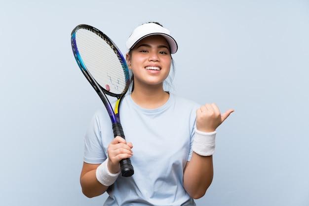 Asiatisches mädchen des jungen jugendlichen, welches das tennis zeigt auf die seite spielt, um ein produkt darzustellen Premium Fotos
