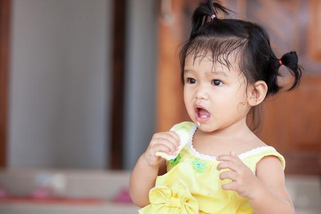 Asiatisches mädchen des netten babys kind, das mango isst Premium Fotos