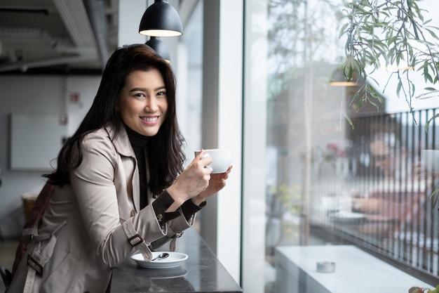 Asiatisches mädchen des schönen porträts, das auf gegenstange in der kaffeestube hält kaffeetasse mit dem lächeln betrachtet kamera sitzt. Premium Fotos