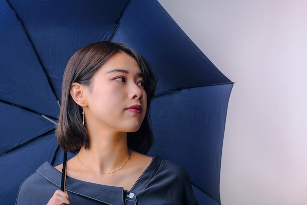 Asiatisches mädchen mit einem regenschirm Premium Fotos
