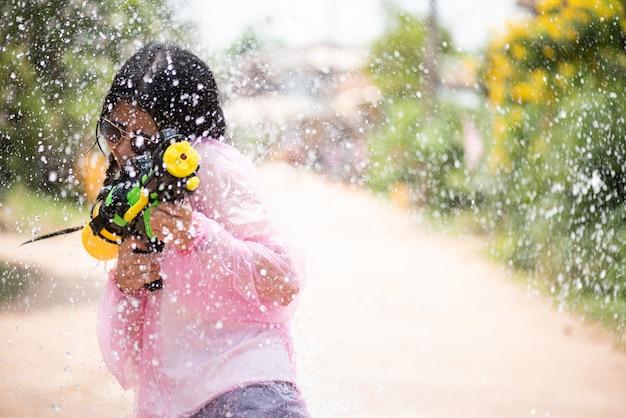 Asiatisches mädchen mit wasserwerfer in songkran-festival - wasserfestival in thailand. Premium Fotos