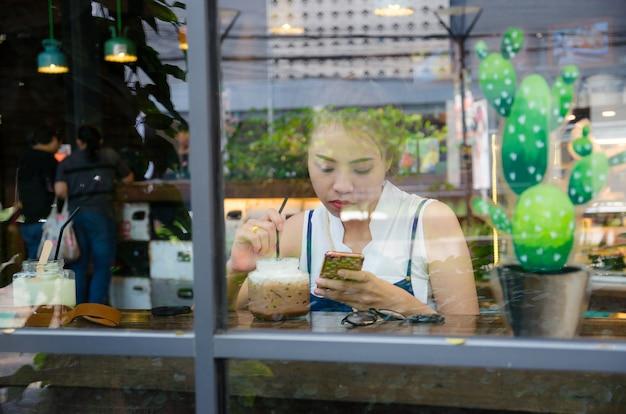 Asiatisches mädchen schaut smartphone im café Premium Fotos