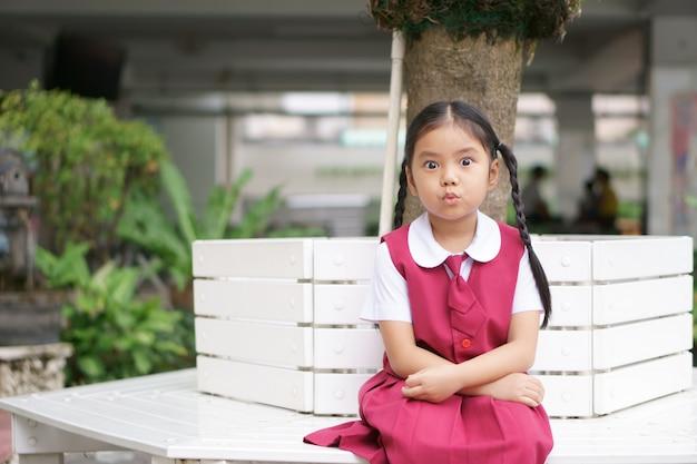 Asiatisches mädchen und student großes auge mit verkürztem mund oder fältchen mit fröhlicher fröhlichkeit und tragen schuluniform Premium Fotos