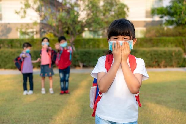 Asiatisches mädchen vorschulkindschüler, der gesundes gesichtsmaskenniesen mit freunden im hintergrund trägt. Premium Fotos