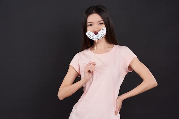 Asiatisches mädchen wirft mit dem lokalisierten cheshire-lächeln auf. Premium Fotos