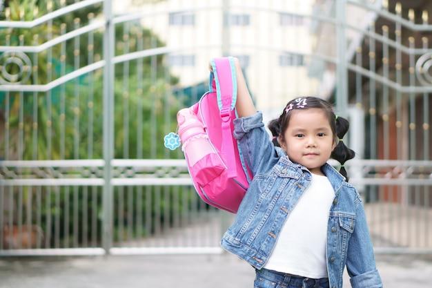 Asiatisches mädchenlächeln und studentenhalten und zeigen rosa schultasche Premium Fotos