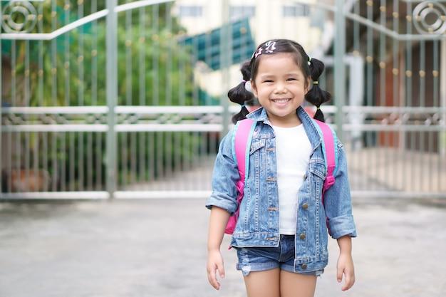 Asiatisches mädchenlächeln und studentenschlinge oder schulterrosa schultasche Premium Fotos