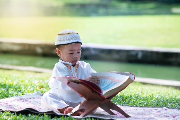Asiatisches moslemisches kind liest den quran im park, islamkonzept, Premium Fotos