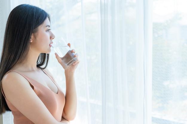 Asiatisches nettes mädchen der schönen schönheitsfrau fühlen sich glücklich, sauberes getränkwasser für gute gesundheit morgens trinkend Kostenlose Fotos