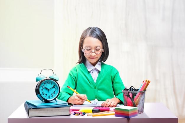 Asiatisches nettes mädchen in den gläsern lernend mit der schule stationär auf dem schreibtisch Premium Fotos
