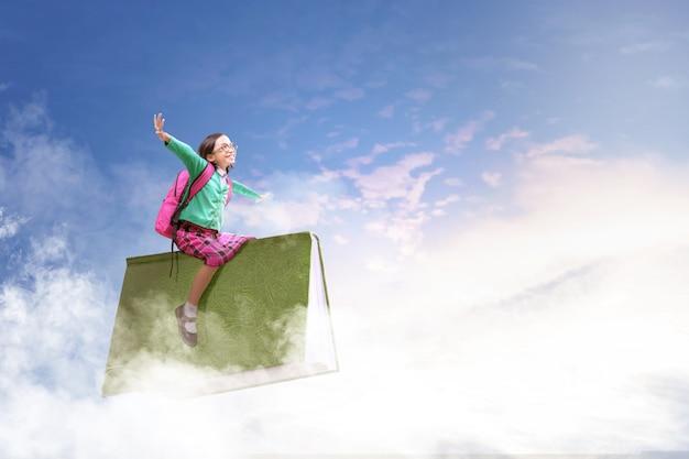 Asiatisches nettes mädchen mit den gläsern und rucksack, die auf dem buch mit blauem himmel sitzen Premium Fotos