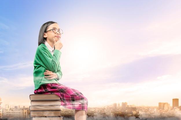 Asiatisches nettes mädchen mit gläsern denken beim sitzen auf dem stapel von büchern mit stadt und blauem himmel Premium Fotos