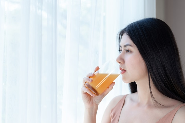 Asiatisches nettes mädchengefühl der schönen schönheitsfrau glücklich, orangensaft für gute gesundheit morgens trinkend Kostenlose Fotos