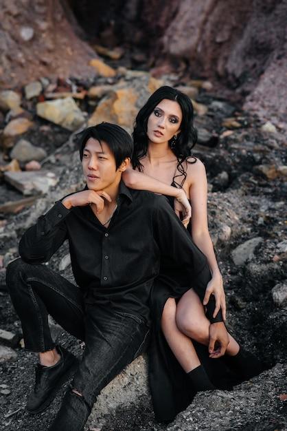 Asiatisches paar in den umarmungen, die auf den felsen sitzen. liebesgeschichte Premium Fotos