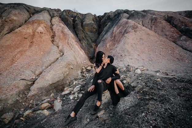 Asiatisches paar in den umarmungen, die auf den felsen sitzen. liebesgeschichte. Premium Fotos