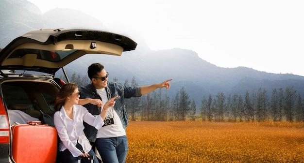 Asiatisches paar mann mit vintage camerra und frau sitzen auf der rückseite des autos Premium Fotos