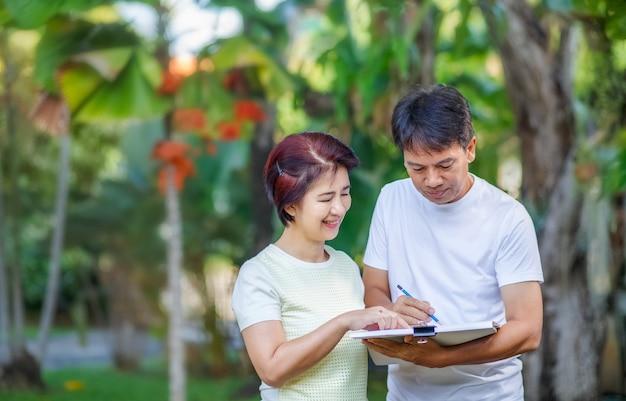 Asiatisches paar mittleren alters, das gartenplan zusammen im hinterhof spricht und entwirft. Premium Fotos