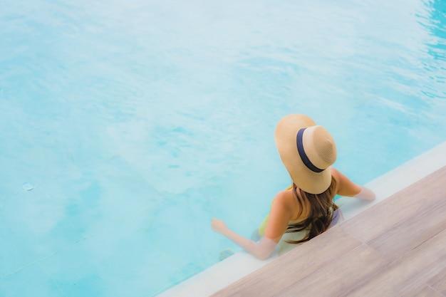 Asiatisches schönes glückliches lächeln der jungen frau des porträts entspannen sich um swimmingpool im freien in den feiertagsferien Kostenlose Fotos