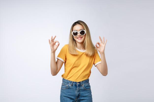 Asiatisches schönes lächeln der jungen frau mit okayfingerzeichenisolat auf weißem hintergrund Premium Fotos