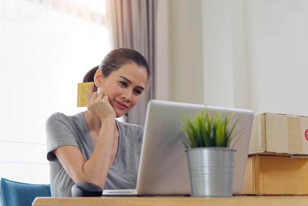Asiatisches schönes mädchen, das online von der website unter verwendung der kreditkarte für zahlung kauft. Premium Fotos