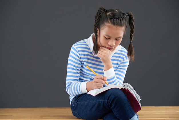 Asiatisches schulmädchen, das auf dem schreibtisch, an hand schreibend in übungsbuch mit dem kinn sich lehnt sitzt Kostenlose Fotos