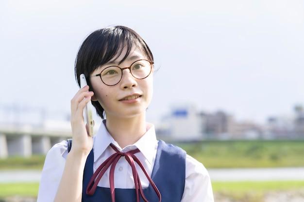 Asiatisches schulmädchen mit schwarzen kurzen haaren, die auf einem smartphone sprechen Premium Fotos