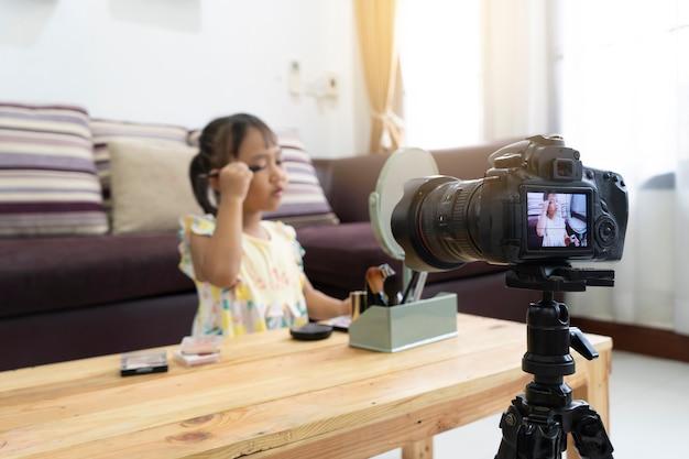 Asiatisches spiel des kleinen mädchens, das ein make-up mit der aufnahme macht videoblogger-kamera macht Premium Fotos