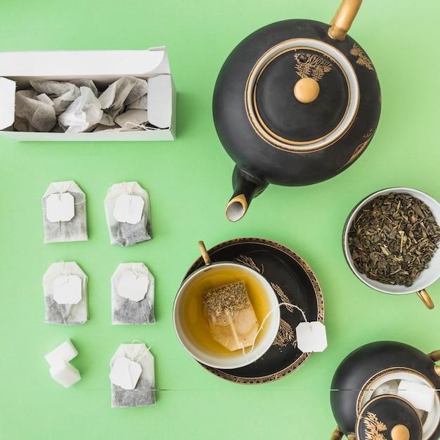 Asiatisches teeset mit kräuterteebeuteln auf grünem hintergrund Kostenlose Fotos