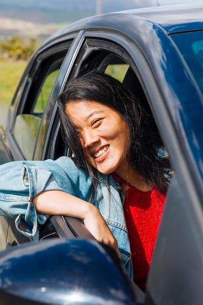 Asiatisches weibliches lächelndes sitzen im auto Kostenlose Fotos