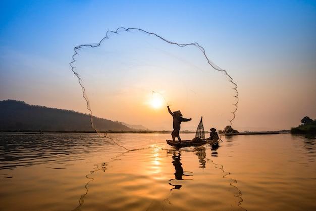 Asien-fischernetz unter verwendung des hölzernen boot casting-netzsonnenuntergangs oder -sonnenaufgangs im mekong Premium Fotos