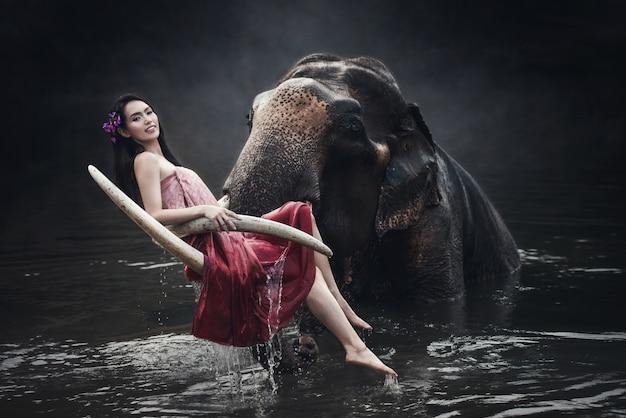 Asien-frau, die das trachtenmode-kostüm sitzt und aufwirft mit großem elefanten im fluss trägt Premium Fotos