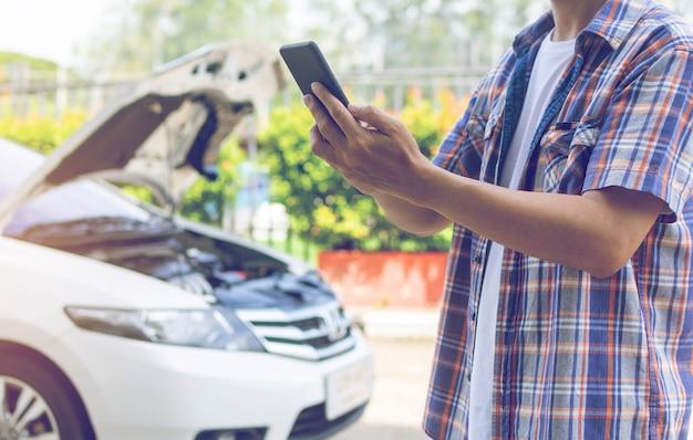 Asien-mannstandfrontseite ein defektes auto, das um unterstützung ruft Premium Fotos