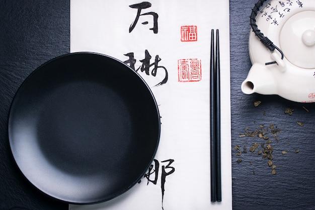 Asien nahrungsmittelzusammensetzung mit chinesischen ess-stäbchen und leeren teller auf einem dunklen stein hintergrund Kostenlose Fotos