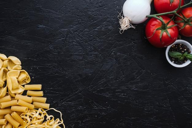 Assorted pasta in der nähe von gemüse und gewürzen Kostenlose Fotos