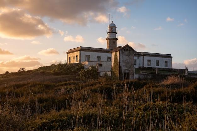 Atemberaubende aufnahme des larino-leuchtturms in galizien, spanien während des sonnenuntergangs Kostenlose Fotos