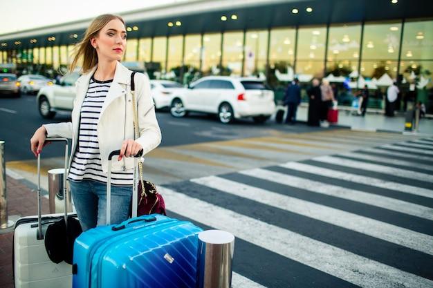 Atemberaubende blonde dame mit blauen und weißen koffern steht vor dem überqueren auf der straße Kostenlose Fotos