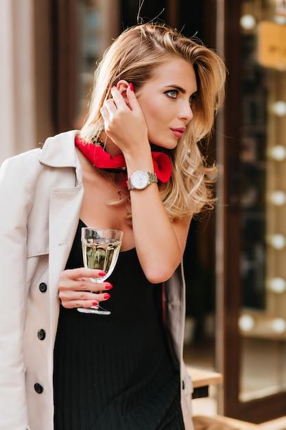 Atemberaubende frau mit trendigem make-up, die ein glas wein hält und ihre blonden haare berührt. außenporträt des glamourösen weiblichen modells mit champagnerbecher. Kostenlose Fotos