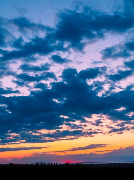 Atemberaubende landschaft der schönen wolken über einem feld mit grünen bäumen Kostenlose Fotos