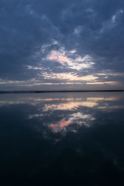 Atemberaubende landschaft des sonnenuntergangshimmels mit sturmwolken, die auf der wasseroberfläche reflektieren Kostenlose Fotos