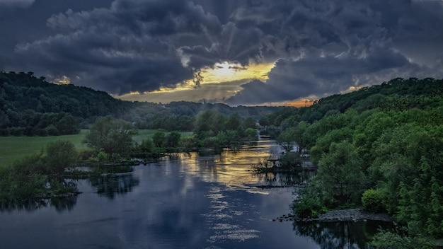 Atemberaubende susnet an einem fluss mitten in einem grünen wald unter dem dunklen himmel Kostenlose Fotos
