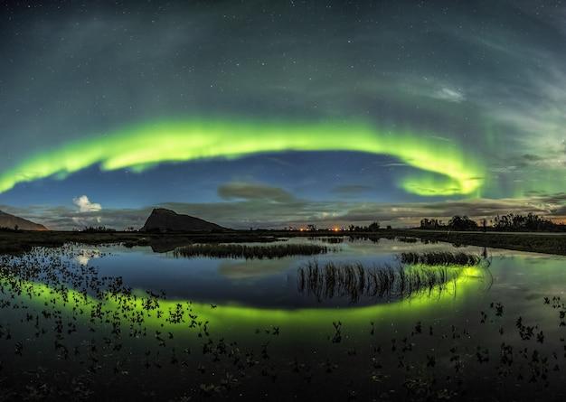 Atemberaubender schuss des windes der farben, die im meer in den lofoten, norwegen reflektieren Kostenlose Fotos