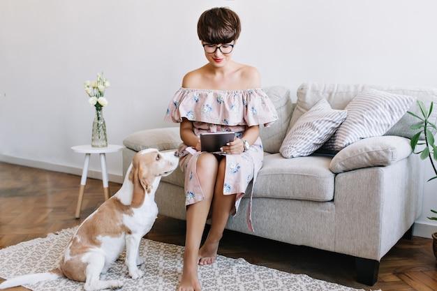 Atemberaubendes brünettes mädchen im stilvollen kleid unter verwendung des internets, während ihr beagle-hund auf spiel wartet. innenporträt der beschäftigten dame in den gläsern, die tablette nahe lustigem welpen halten Kostenlose Fotos