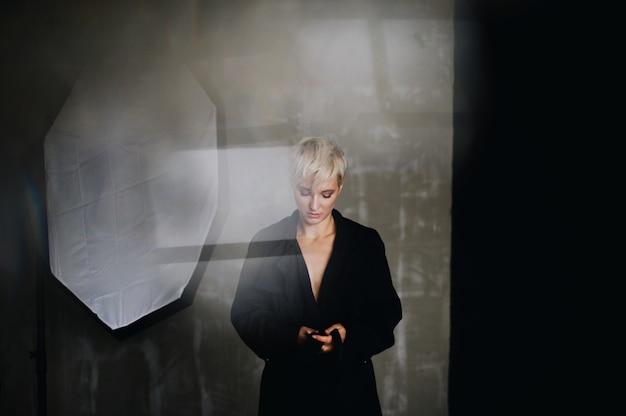 Atemberaubendes modell mit kurzen weißen haaren posiert im schwarzen mantel vor einer soft-box Kostenlose Fotos