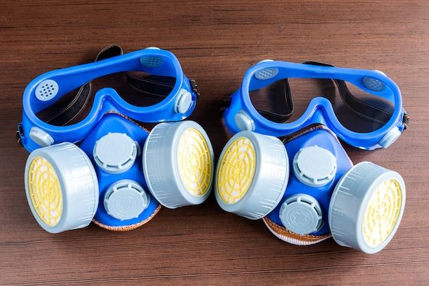 Atemschutzmaske, staubmaske und sicherheitsmaske für chemische industrie auf hölzernem hintergrund. Premium Fotos